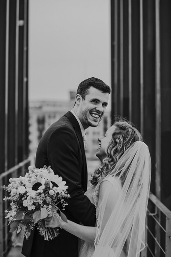 A groom smiles at the camera on the bride at Kadish Park