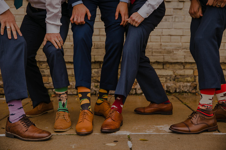 A close up of men showing off their dressy socks