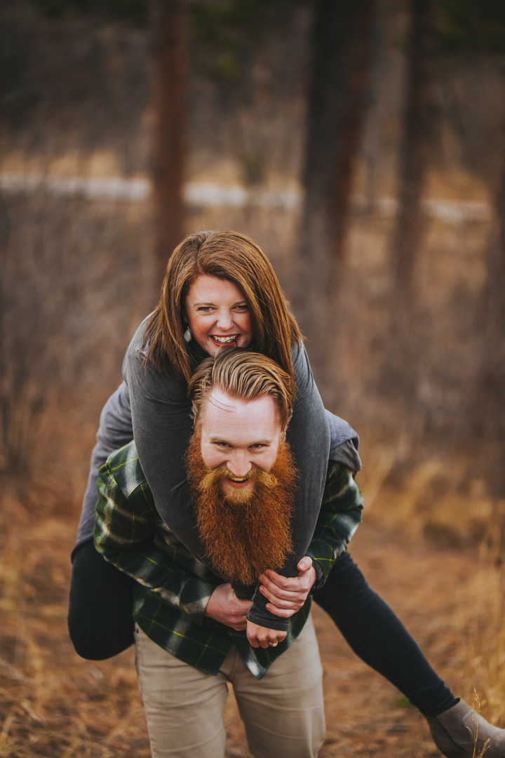 A man give a woman a piggy back ride in a Cheyenne Mountain State Park engagement session in Colorado Springs, Colorado