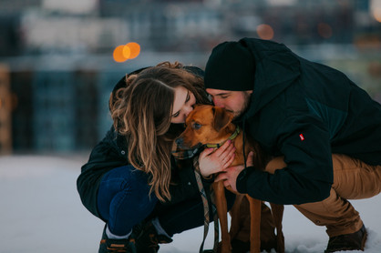 A woman and man kneel next to a dog in front of the Milwaukee skyline