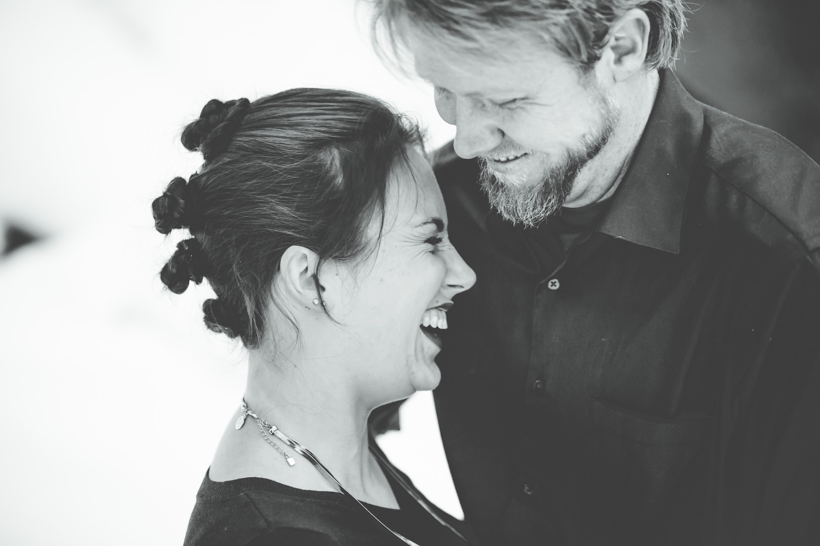 A close up of a woman laughing into a mans' chest at a Horsethief Falls Divide, Colorado engagement session