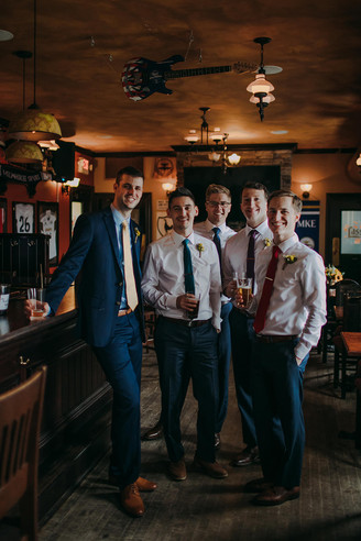 A group of men smile at the camera of a Milwaukee Wedding Photographer