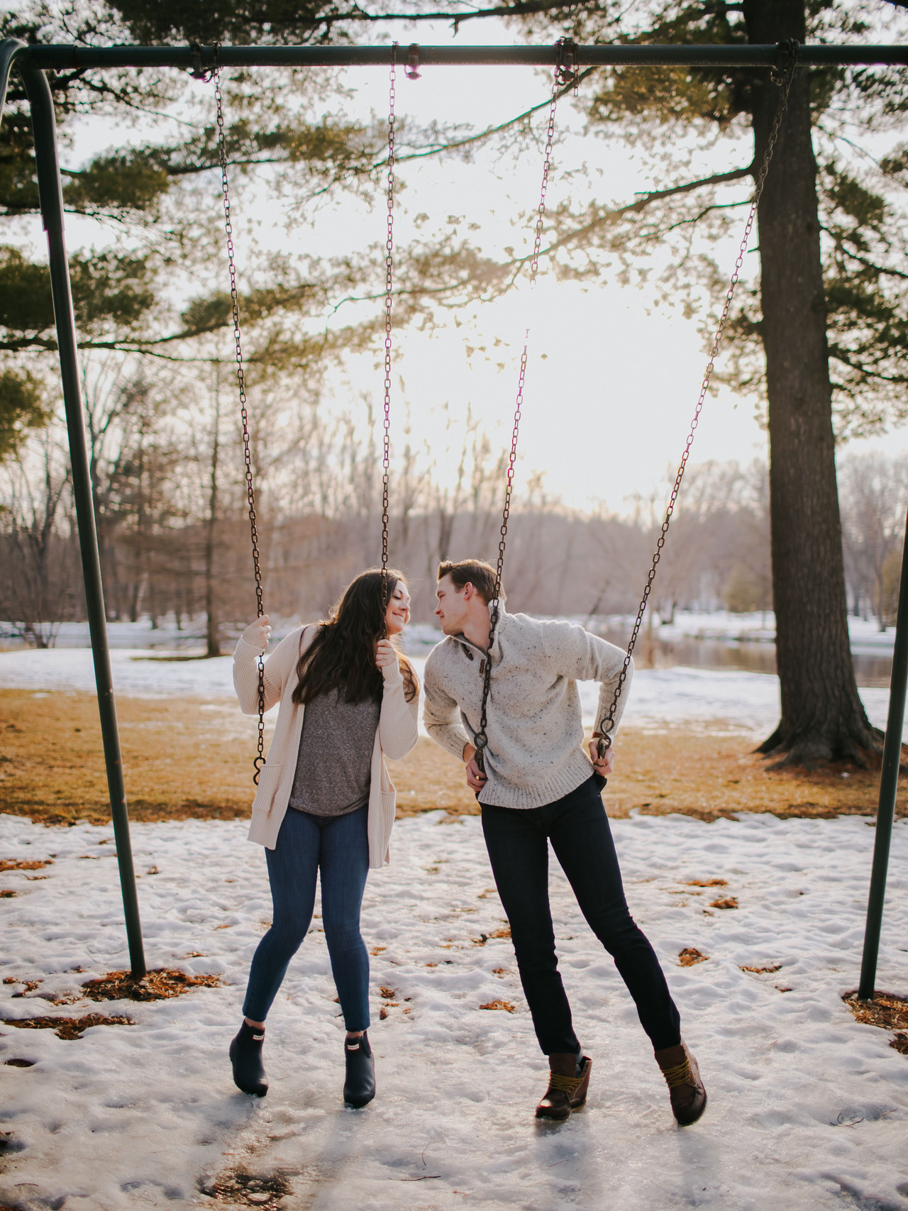 A man and woman lean in for a kiss on a swingset during Stevens Point engagement photos