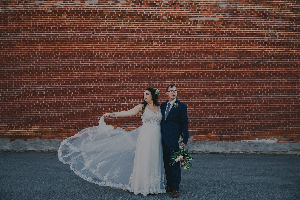 A Bride and Groom pose in front of an urban brick wall during a Milwaukee Wisconsin wedding