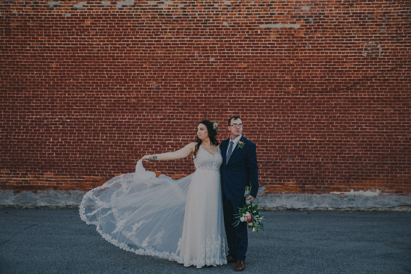 A bride fans her dress tulle out as her and her groom stand in front of a brick wall in Cashton Wisconsin