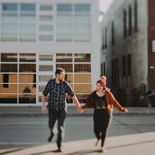 A man and woman hold hands and run across Main Street in Historic Downtown Stevens Point