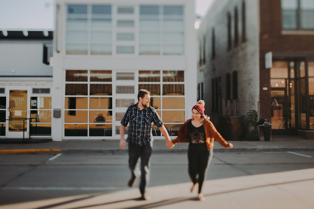 A man and woman hold hands as they run across Main Street during a Downtown Stevens Point engagement session
