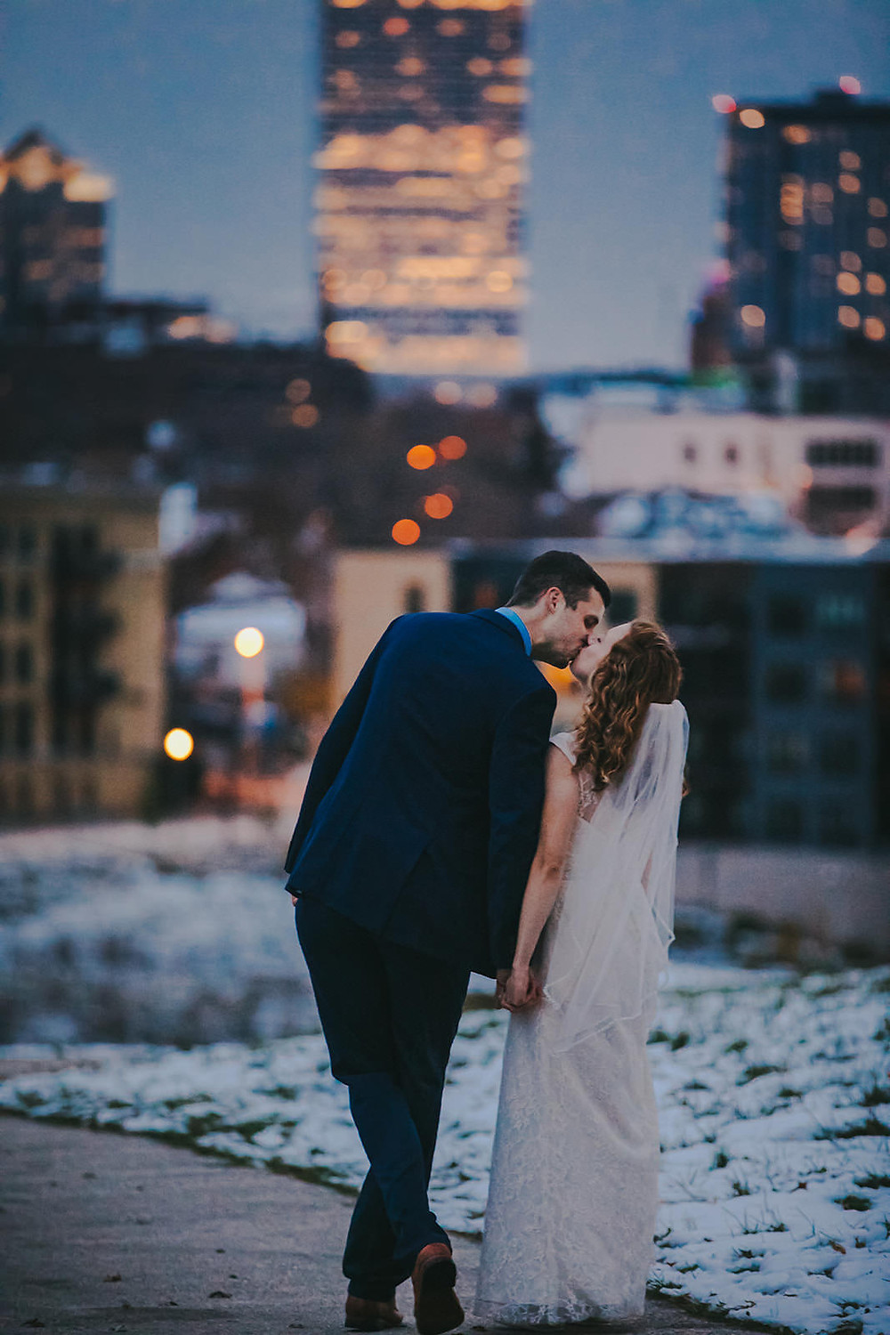 A man and woman kiss in front of the downtown Milwaukee skyline during a downtown Milwaukee wedding