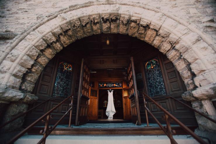 A bridal dress hangs in a church doorway