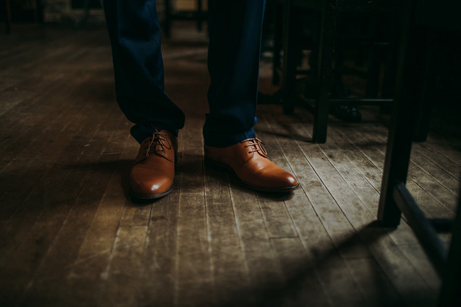 A closeup of a man's shoes on a scuffed wooden floor