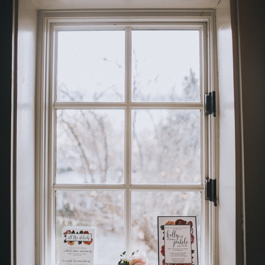 Handmade wedding invitations propped inside a white window frame at the Covenant at Murray Mansion in Racine, Wisconsin