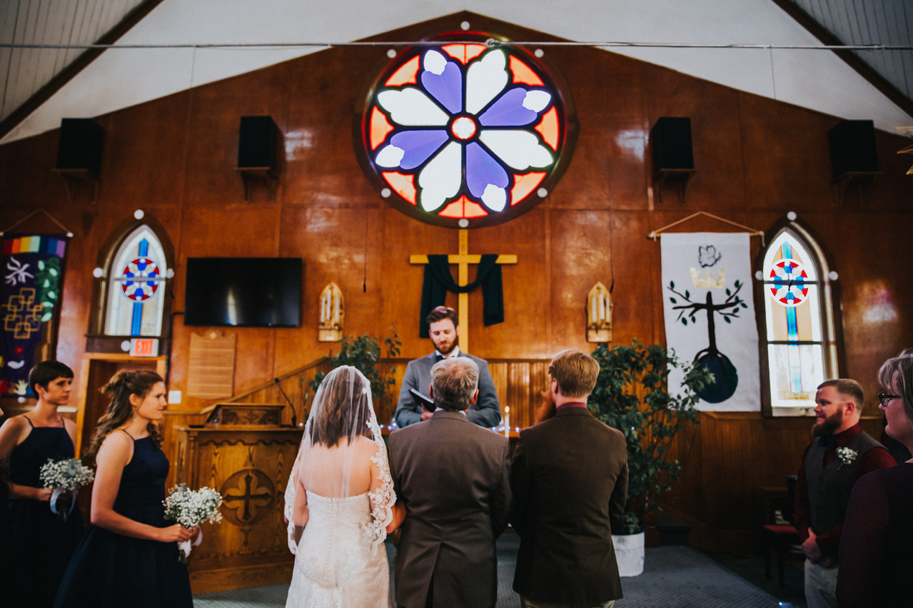 A father gives his daughters hand in marriage away to his future son-in-law at Union Congregational Church in Crested Butte Colorado
