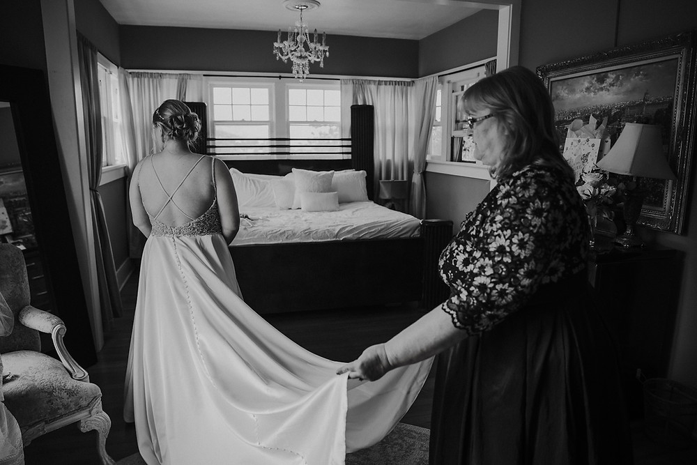 A woman holds the train of a bride's wedding gown - Wisconsin Wedding Photographers
