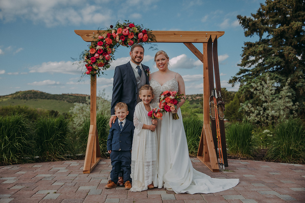 A bride, groom, ring bearer, and flower girl stand in front of a wooden arch covered in flowers at The Manor House wedding