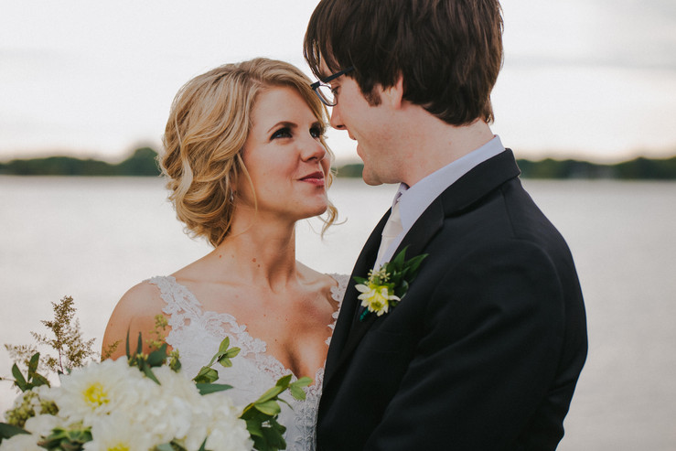 A bride and groom look into each others eyes while posing for Oshkosh wedding photographers
