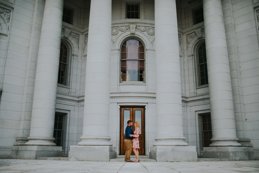 A man and woman hug each other in front of the Madison Capitol Building
