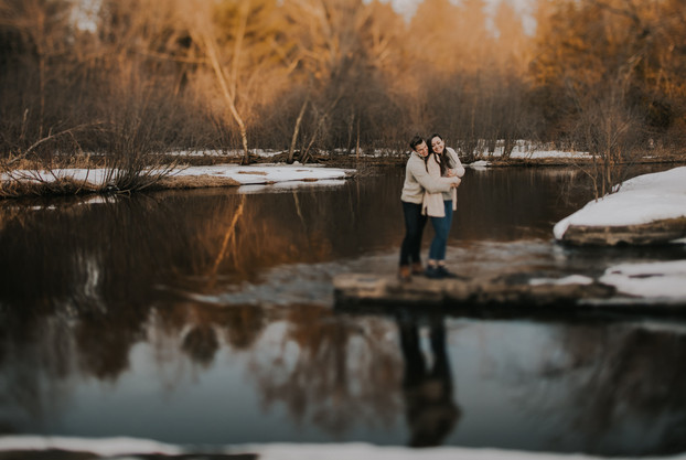 A couple stands along the Plover River