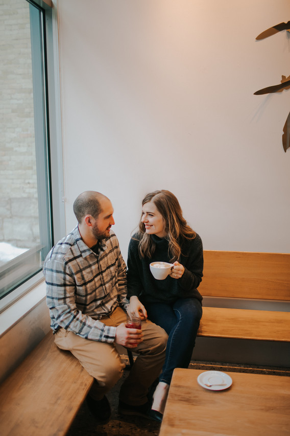 A man and woman smile at each other as they enjoy coffee at Kickapoo Coffee in Milwaukee Wisconsin