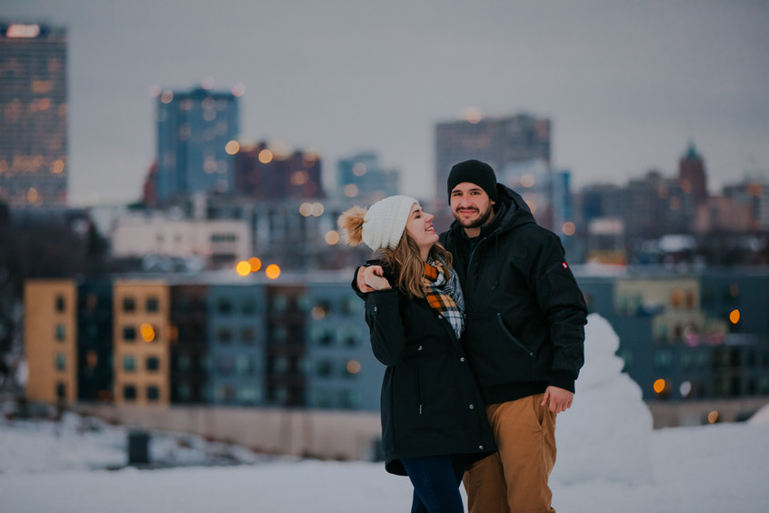 A man and woman pose for Milwaukee skyline engagement photos