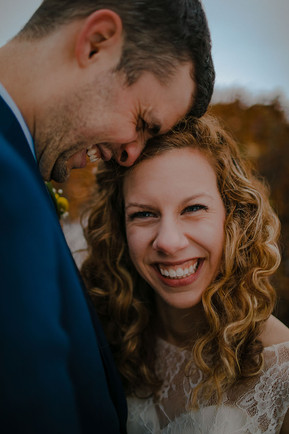 A close up of a bride smiling at the camera as her groom nuzzles her forehead in Kadish Park