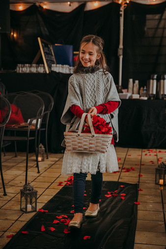 Flower girl spreads rose petals down the aisle of a Milwaukee wedding ceremony