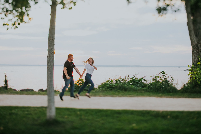 A man and woman run hand in hand at Tenney Park
