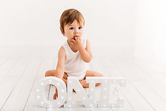 Baby sitting next to letters spelling ONE in cake smash photo session with Rachel Fairfield Photography