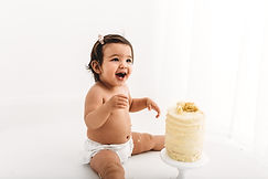 Baby girl laughing next to a cake during a cake smash photo shoot with Rachel Fairfield Photography