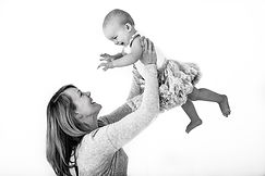 mum holding toddler up in the air in photoshoot in Rachel Fairfield's studio in Surrey