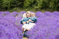 mum cuddling her two little girls in Mayfield Lavender fields on outdoor photoshoot