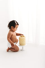 baby girl trying cake for the first time during a cake smash session with Rachel Fairfield Photography