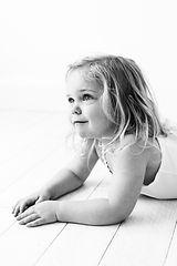 toddler girl lying on floor smiling in photoshoot with surrey photographer Rachel Fairfield Photography
