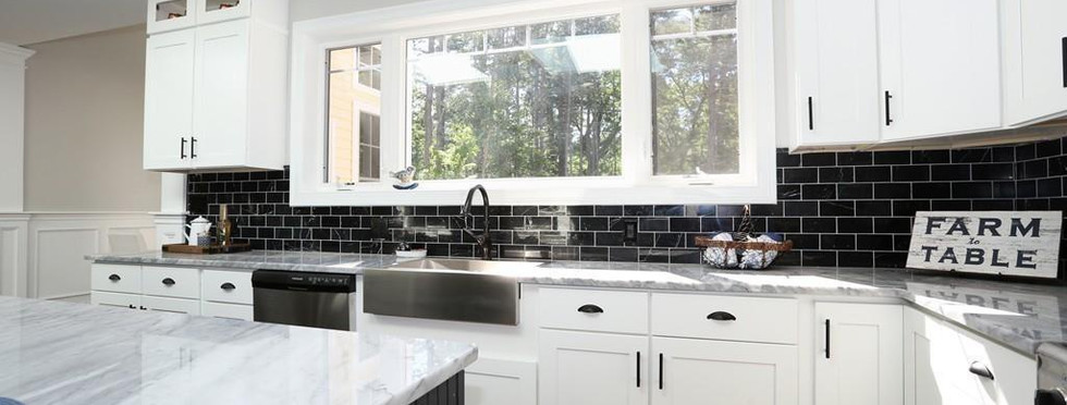 Stainless Steel Farmhouse Sink with Black Subway Tiled Backsplash