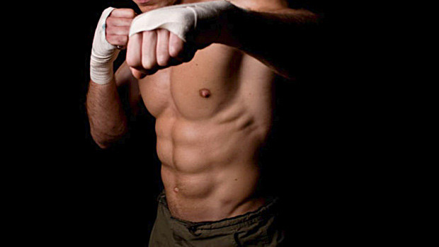 Man with abs and wrapped hands in fighting stance