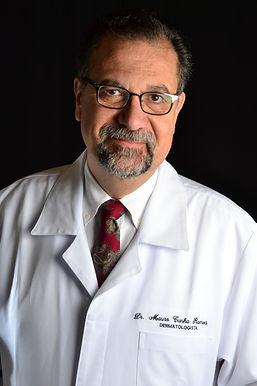 Fotografia do Dr. Mauro usando gravata, avental branco e uniforme de trabalho.
