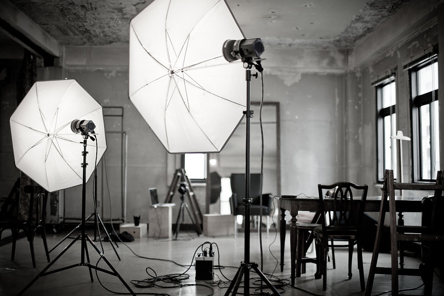 A concrete photo studio featuring strobe lights with umbrella reflectors