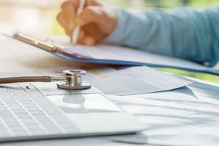 Doctor working in hospital writing presc