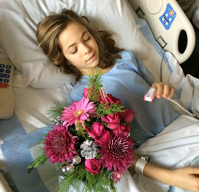 Malia lying in the hospital bed looking at flowers
