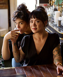 Two young women share a cocktail. They look directly into the camera and embrace comfortably as though old friends