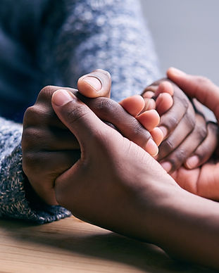 Two people hold each others hands warmly. They look to be comforting each other. Each person is from a different background showing a bridging and understanding of each other on a friendly and respectful level.