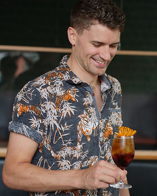A handome young bartender looks down proudly at the cocktail he holds in his hands. He wears a bright and exciting hawaiian style shirt and has his hair neatly styled