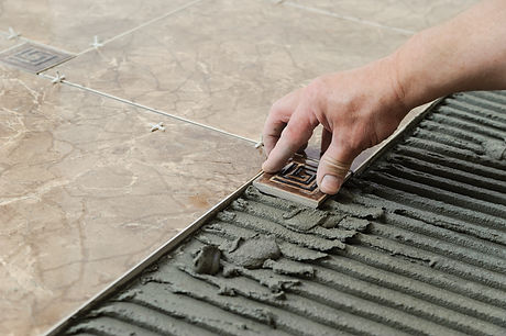 Man placing ceramic floor tile in position over adhesive