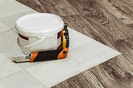 Tool and a container of glue for laying linoleum flooring.jpg