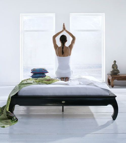 Woman doing yoga pose in bed