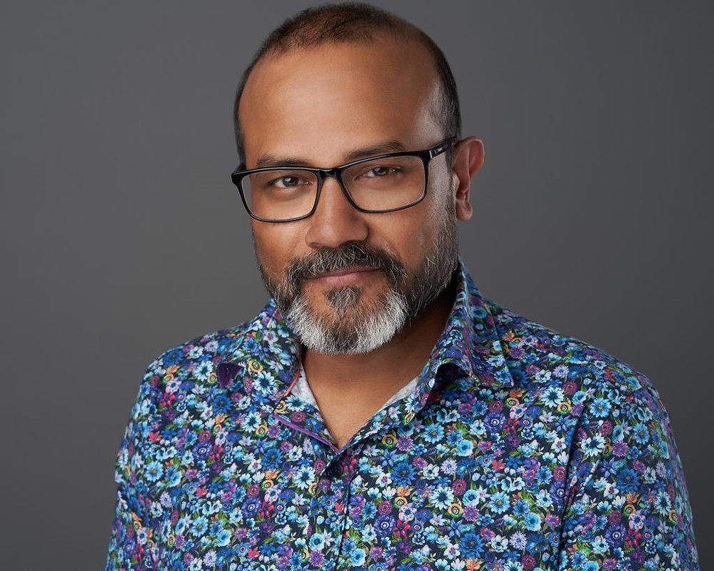Man in glasses and floral shirt smiles at the camera