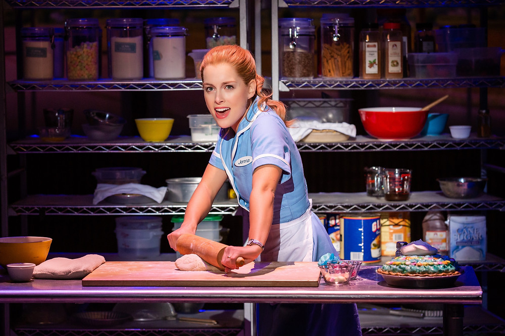 Woman in blue uniform and apron with rolling pin singing