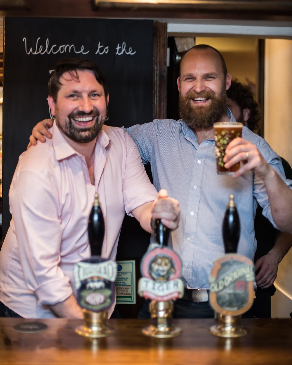 Two men in shirts smiling and pulling pints in a pub