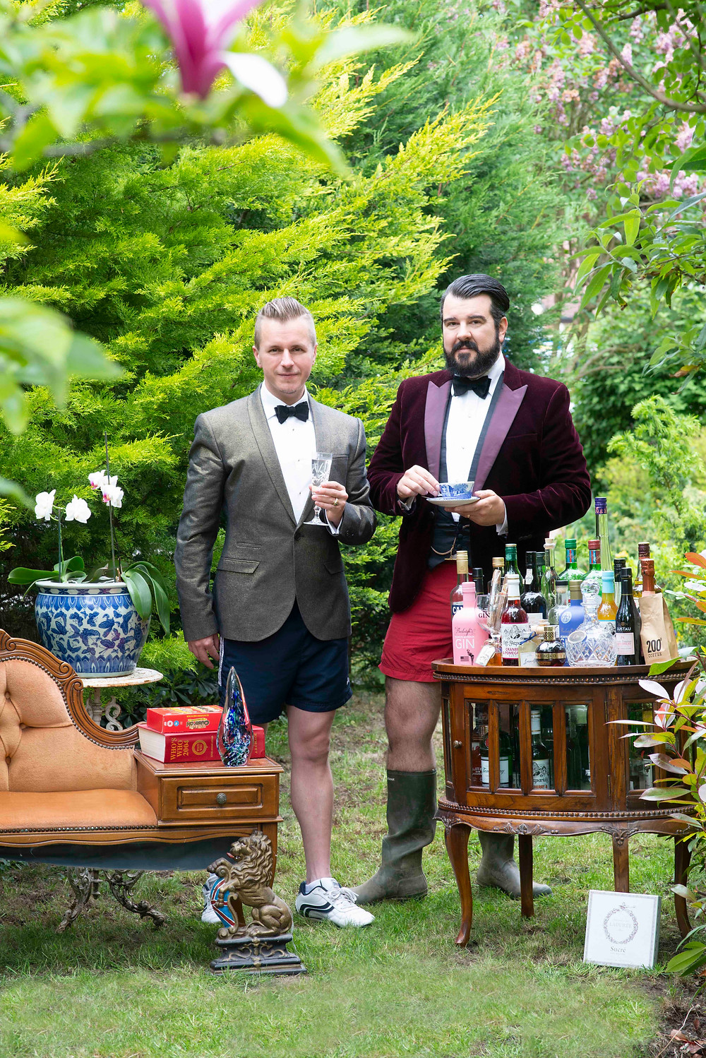 Two men wearing suit jackets and shorts standing in the garden drinking cocktails