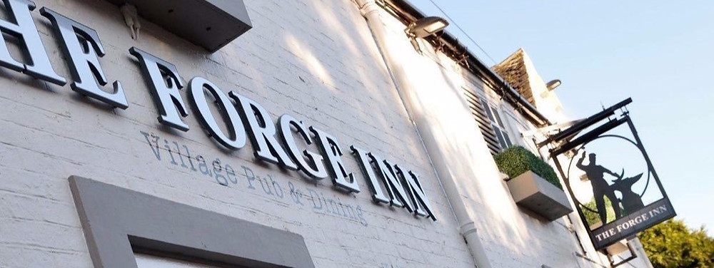 Village pub sign reads 'The Forge Inn'