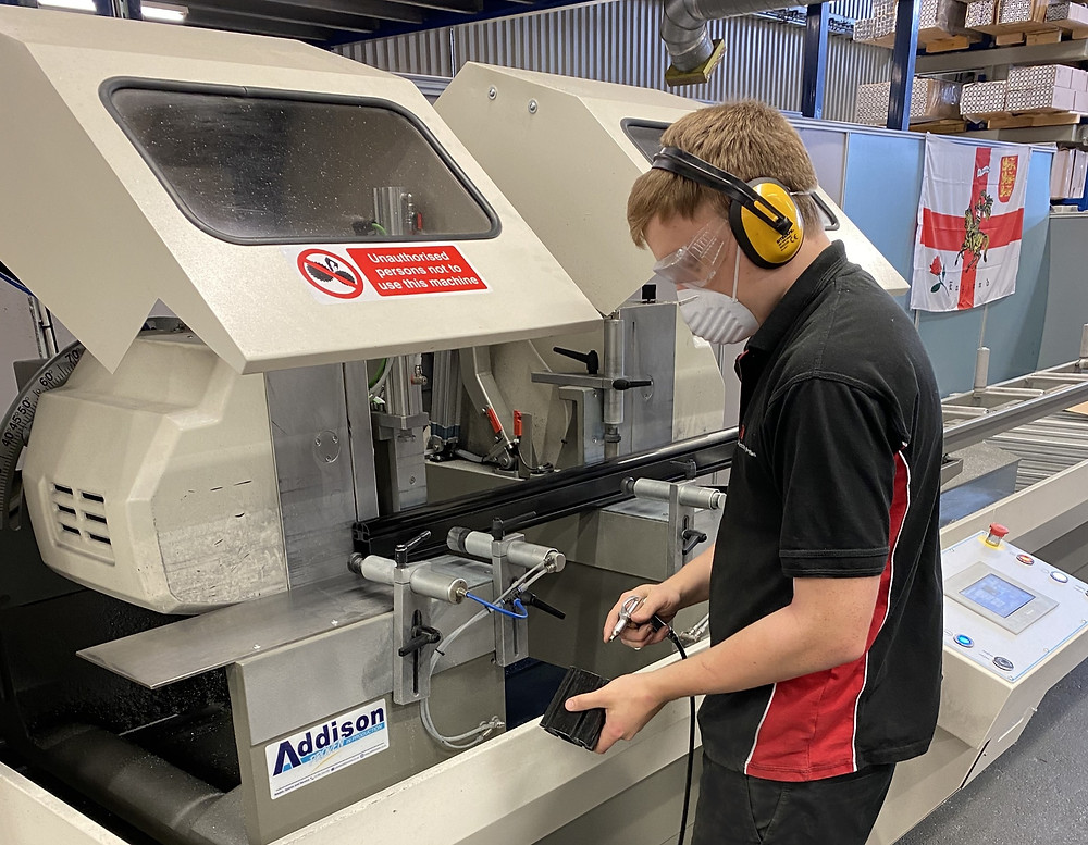 Apprentice working at machine with protective headphones, mask, and glasses